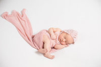 Newborn girl with pink bonnet and knit outfit