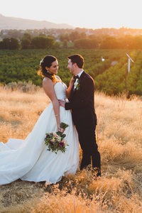 Bride and Groom hugging in the sunset in front of an orchard at Klipsun Cottage in Benton City