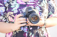 A photographer holds her camera in Downtown Main Street, Wauchula, Florida.