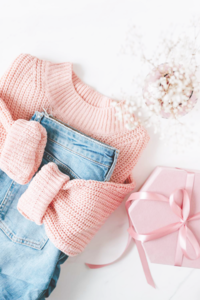 Flatlay of pink jumper, jeans and flowers