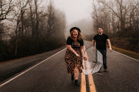 J.Michelle Photography captures a couple running down the road in Hiawassee, Ga during their rainy engagement session