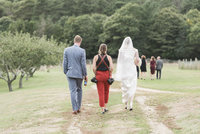 Photographer walking with bride and groom