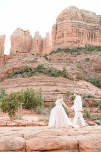 Elopement couple walks in front of Cathedral Rock Sedona