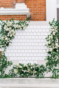 linen covered escort card display with large greenery and floral designs at the monastery event center by cincinnati wedding florist roots floral design