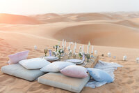 Sweetheart picnic table amidst the Arabian desert dunes, photoshoot organized by Lovely & Planned