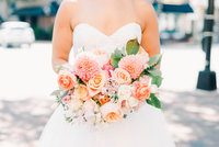 Bride holding beautiful coral, pink, and blush bouquet