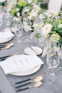 muted blue and grey place setting with grey velvet table linen and modern flatware