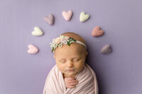 newborn girl swaddled on purple background with felted hearts