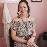 Makeup artist, Jennifer Pitt, smiles for headshot in front of pink wall