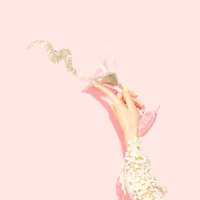 Lady tipping glass of gold glitter against pink background