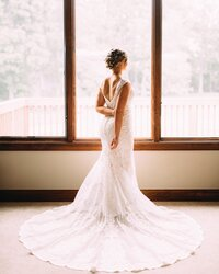 bride standing in front of windows