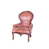 Light pink velvet tufted chair with dark wood trim.