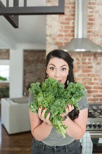 lady holding kale in front of her face for fun headshots