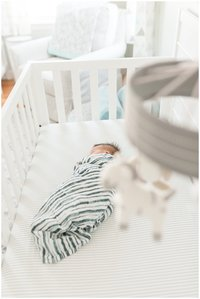 newborn in crib during photos natick