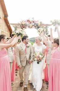 Bride and groom walking under pink flower arch on wedding day