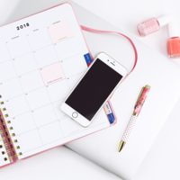 Overview of planner, phone, pens on a white desk