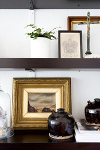 Dark brown bookshelves with gold framed oil painting, and vintage pottery