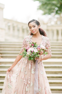 Beautiful bride in blush dress holds skirt and bouquet on staircase