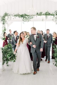 bride and groom walking with wedding party at winter wedding at the grand ivory venue by dallas wedding photographer catie ann photography