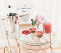 Gold bar cart holding beverage accessories at baby shower