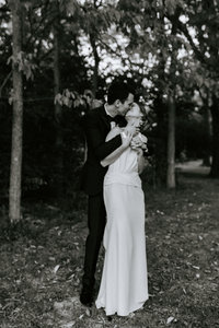 bride and groom kiss in black and white before their wedding reception at historic rosemont springs in berryville virginia