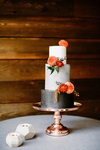 Three tier white and black wedding cake with bright orange flowers and copper cake stand