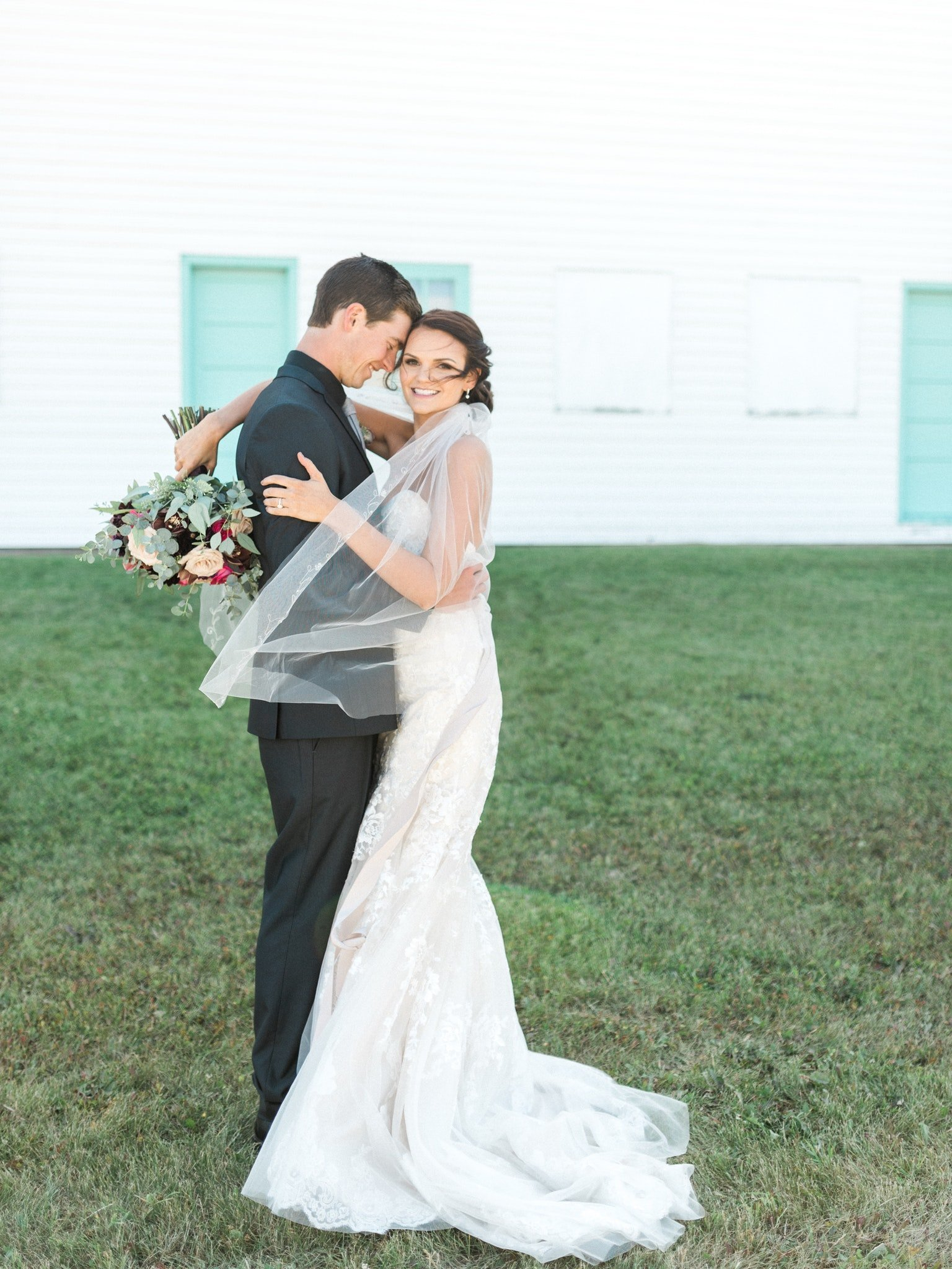 Groom and bride embrace while holding florals