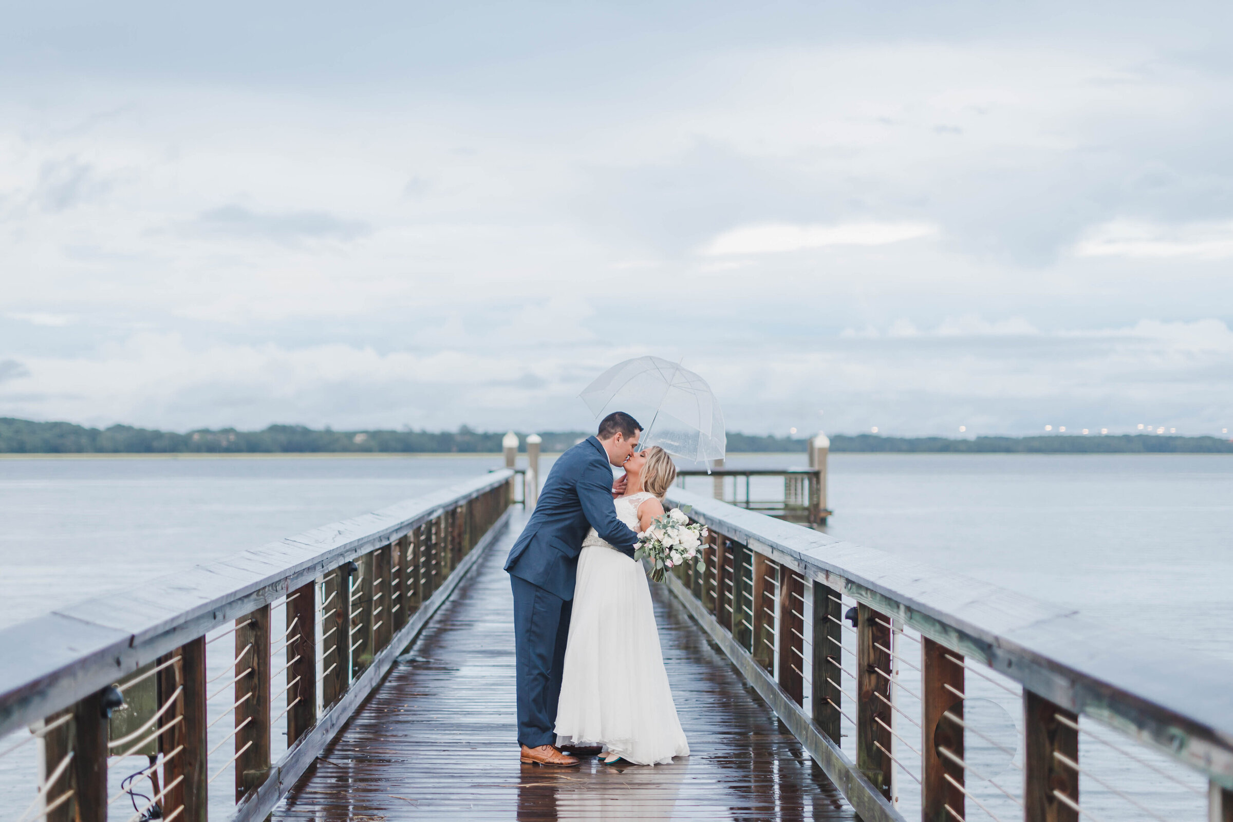 bride and groom kissing on dock daniel island