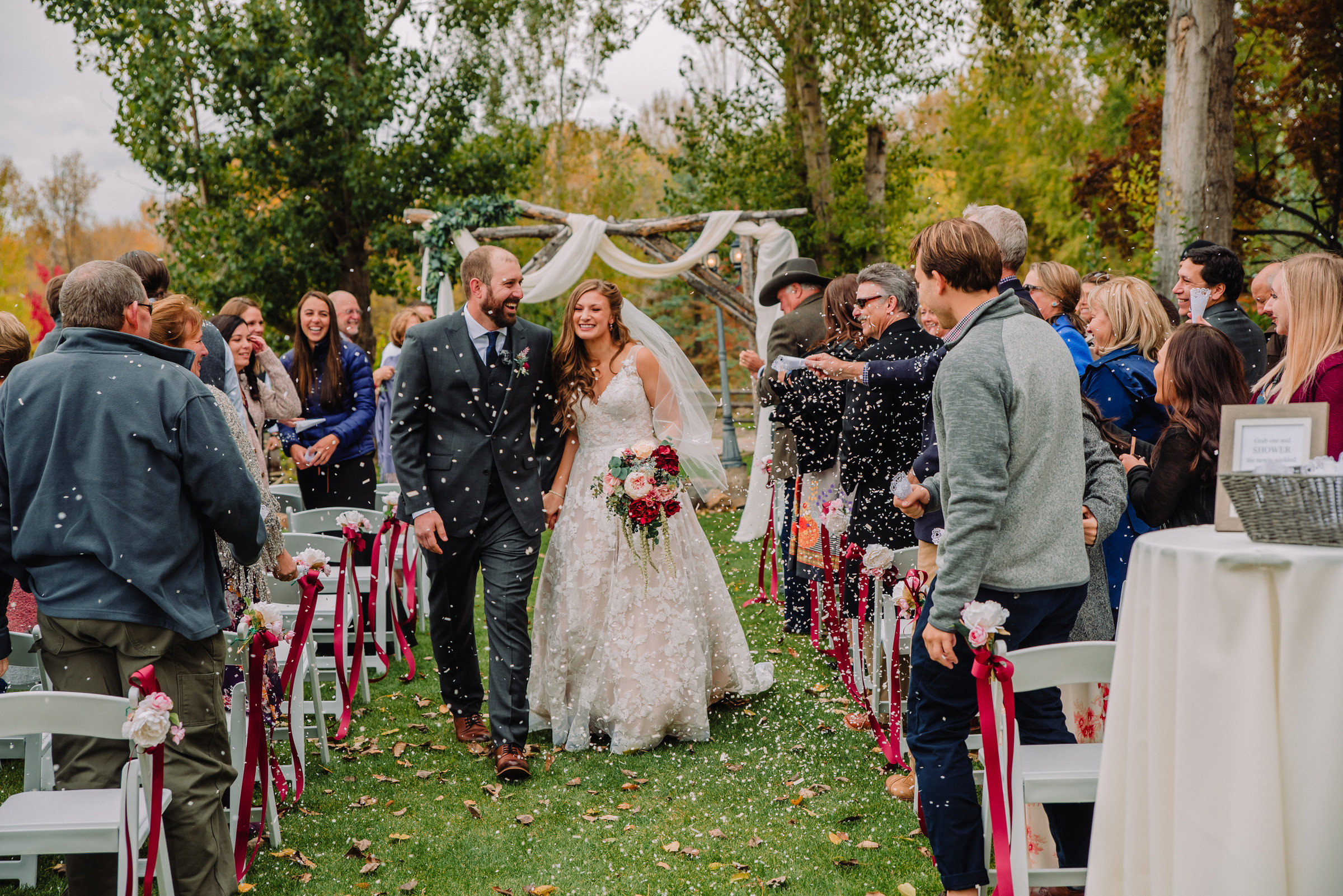 bride and groom walk down the aisle amid confetti at their idaho destination wedding
