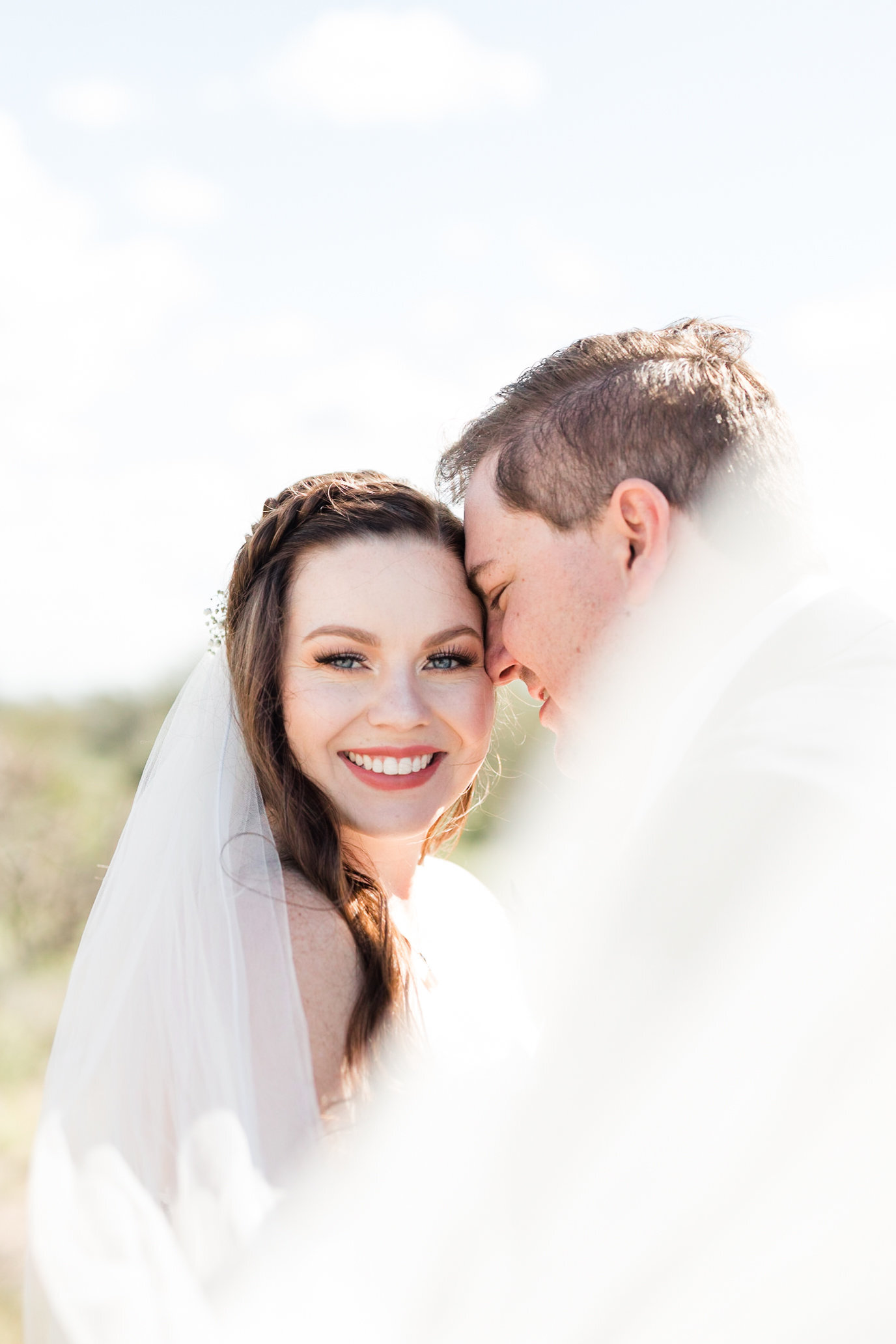A swooping veil that leads to a bride smiling at the camera
