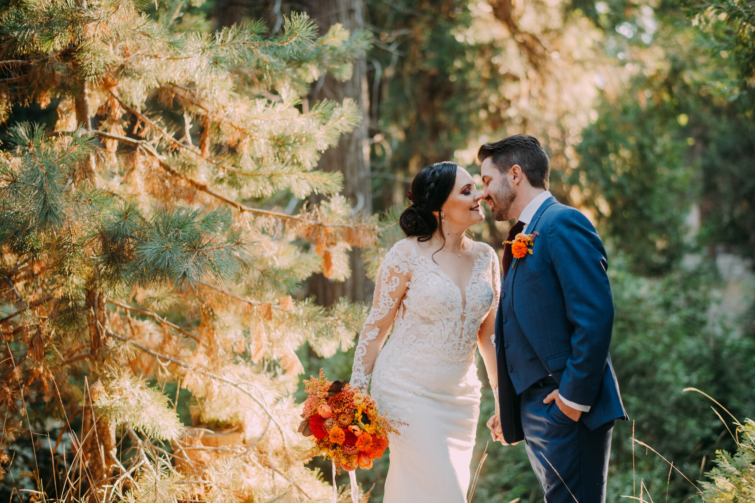 bride holding orange red and brown bouqet wearing white wedding dress leans in to kiss groom wearing blue tux and orange boutonnière in front of a pine tree shot by philadelphia wedding photographer alex medvick