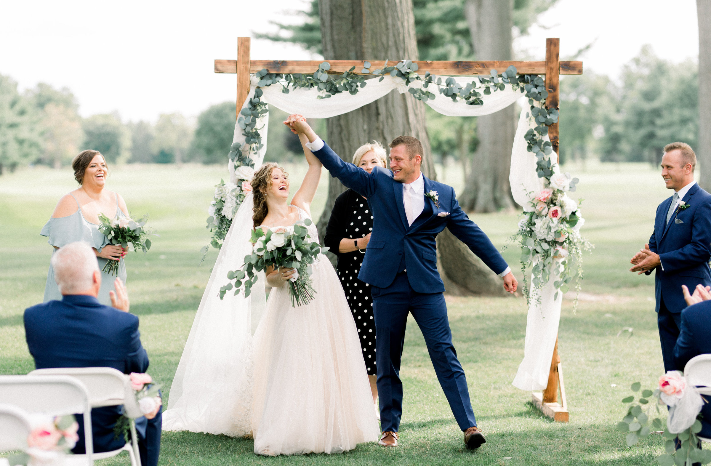 Bride and groom share excitement as they wrap up their wedding ceremony at Owosso Country Club in Lansing Michigan photo by Wedding Photographer in Grand Rapids, Cynthia Boyle