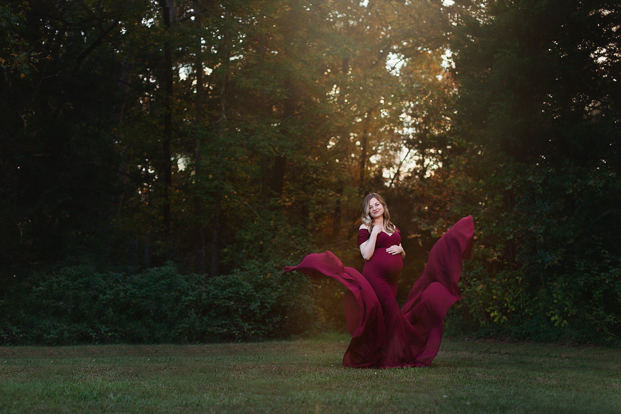 pregnant mom in burgundy gown at fisher farm park charlotte maternity photographer