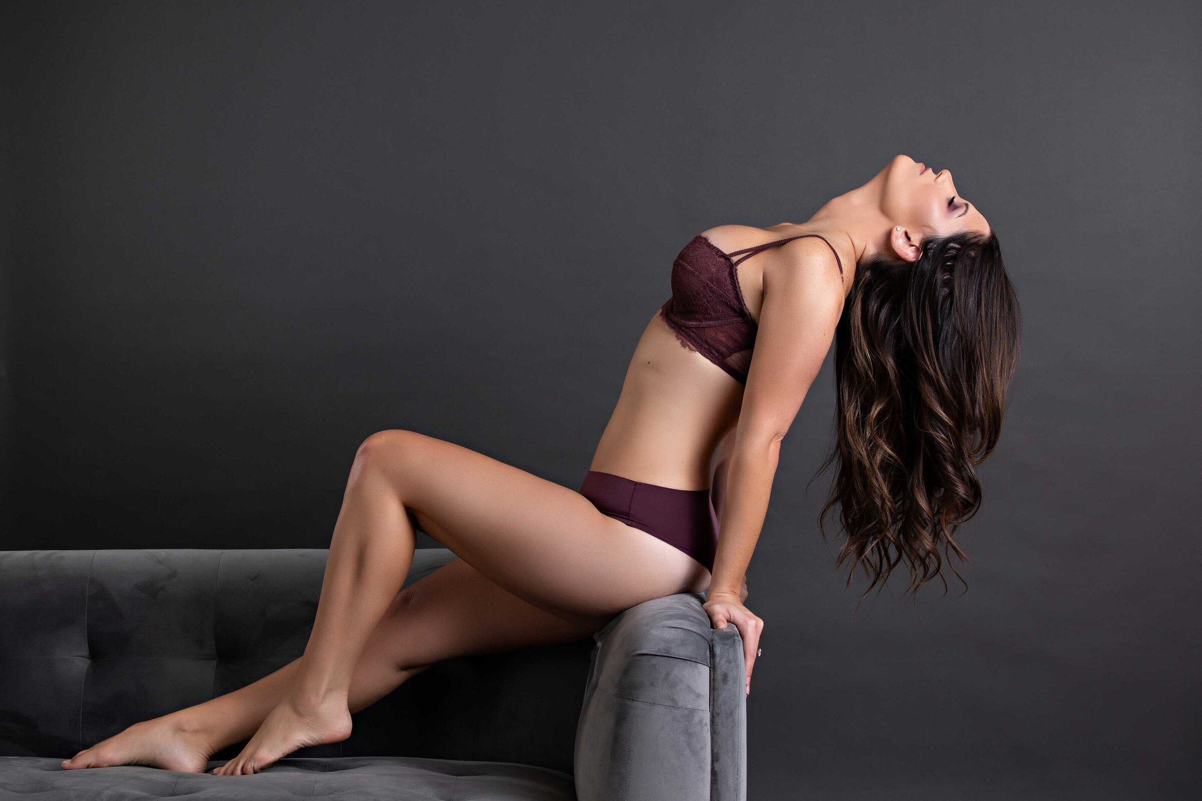 maroon bra set on woman leaning off grey velvet couch