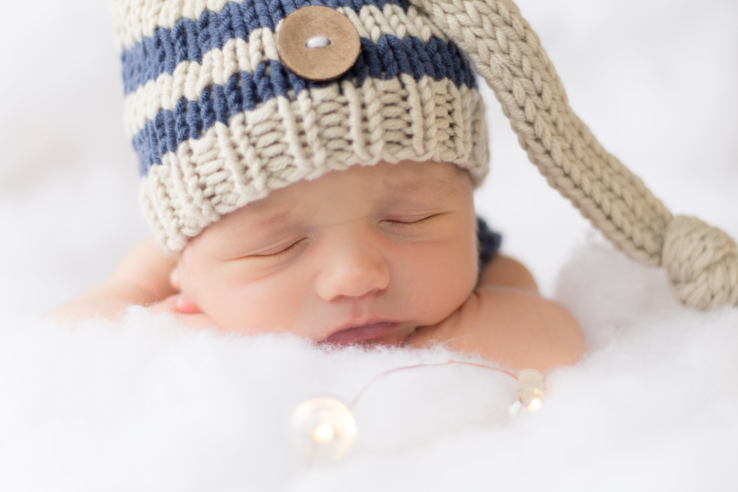 Newborn Baby Boy Wearing blue and tan striped sleep cap