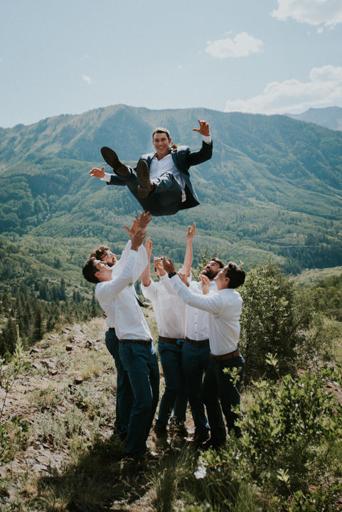 tossing groom in the air, blue suit, white dress shirts, mountaintop wedding photographers, adventure elopement photographers, salty spruce studio, colorado wedding photographers, colorado wedding photography