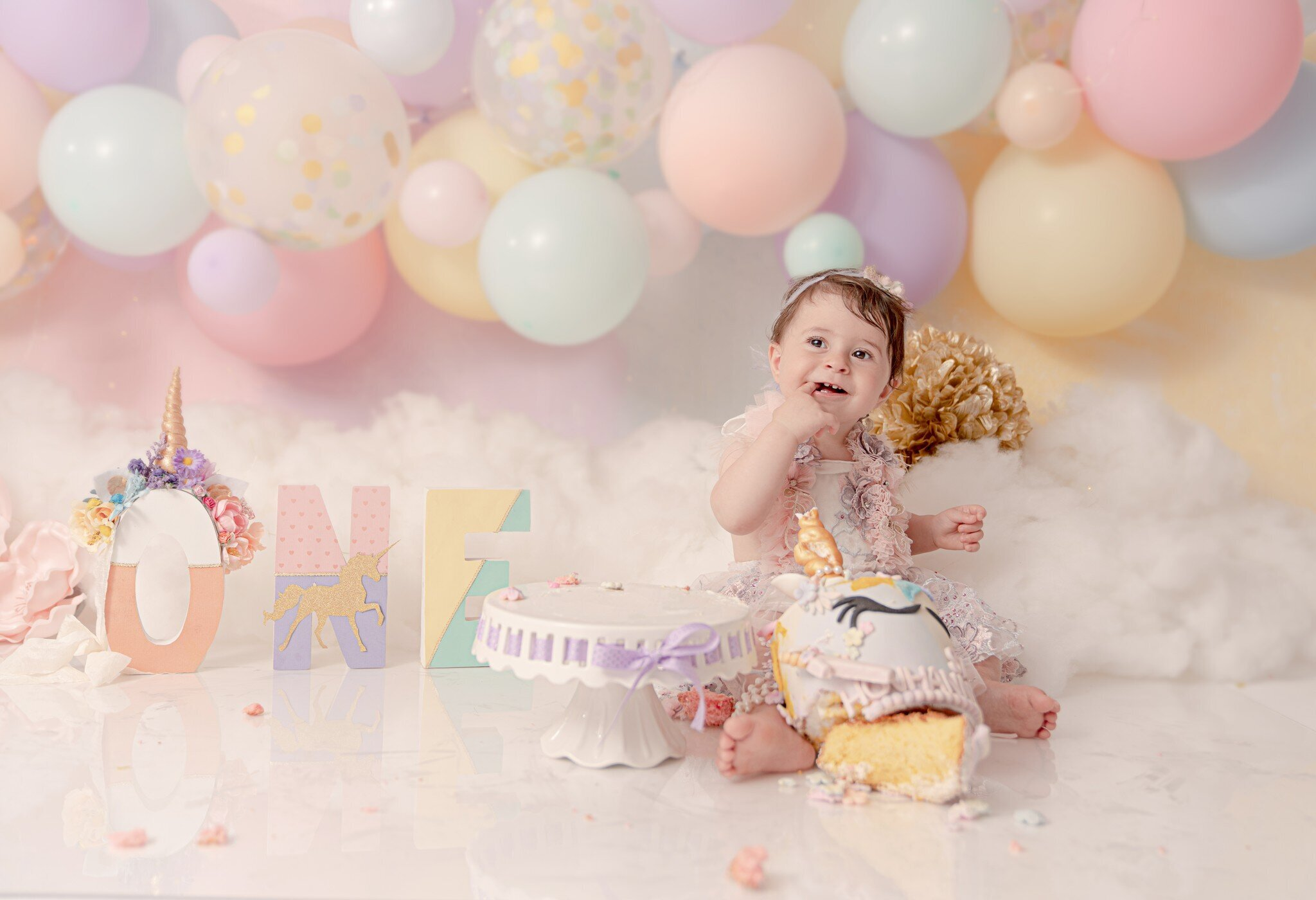 Little girl photoshoot with color balloons and a big cake