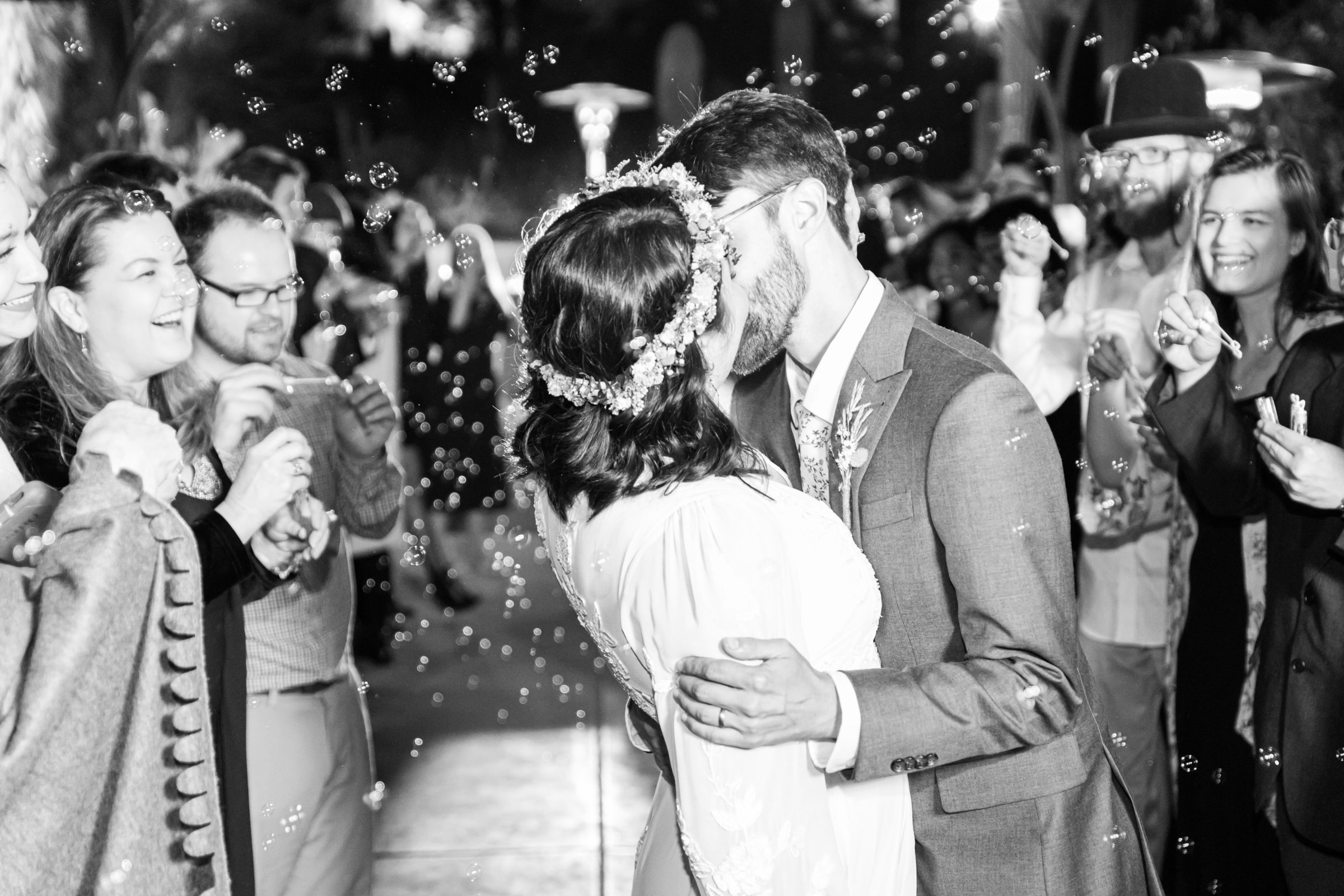 Bride and groom kiss at the end of their wedding with bubbles flying everywhere