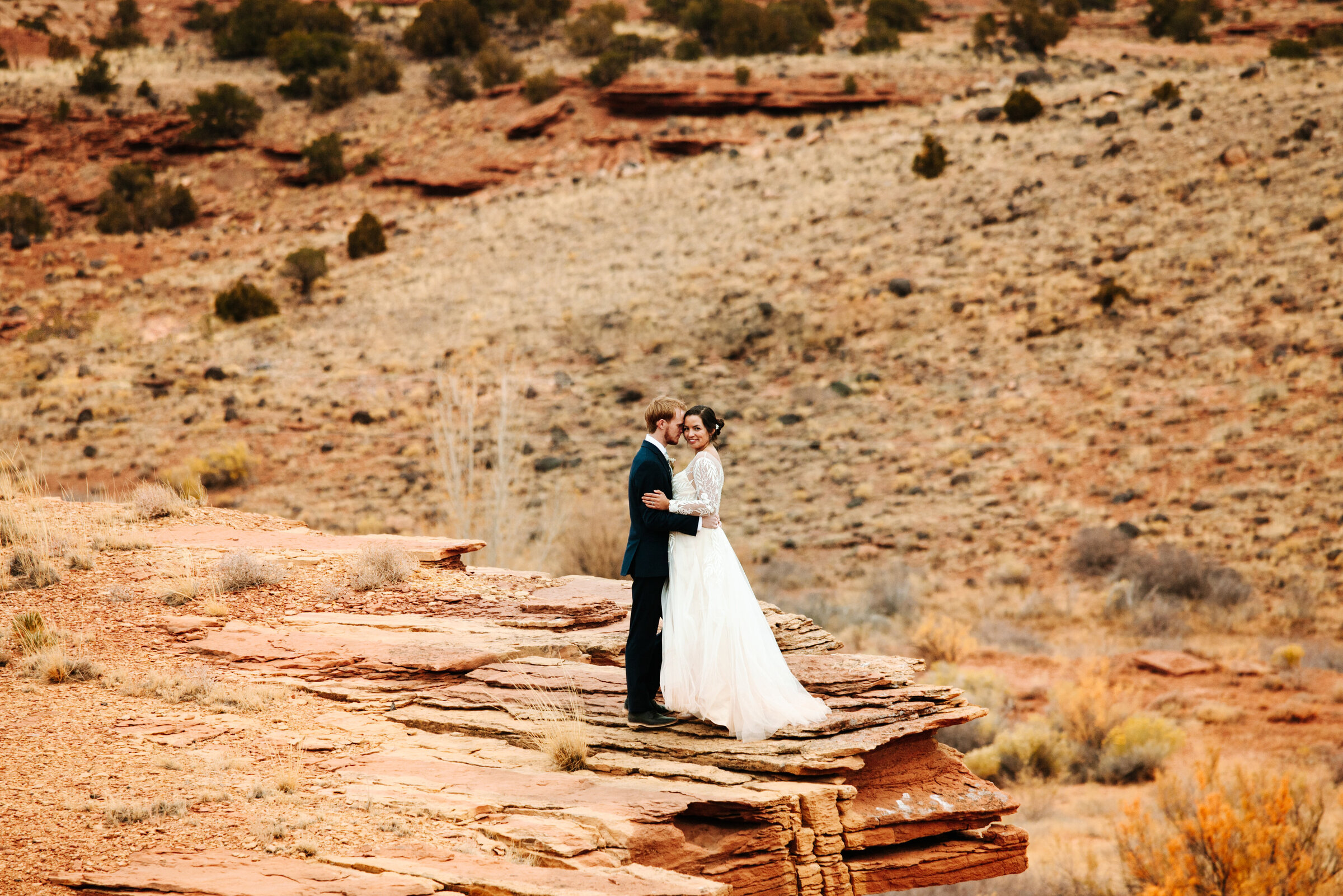 Bride and groom stand on a red rock cliff in Capitol Reef National Park near Moab, Utah holding each other closely. The bride is looking at the camera.