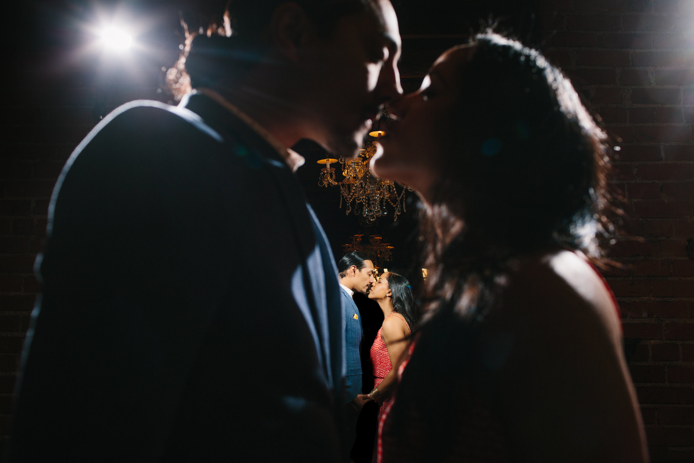 A creative engagement photo with couple kissing in mirror at Carondelet House in Los Angeles