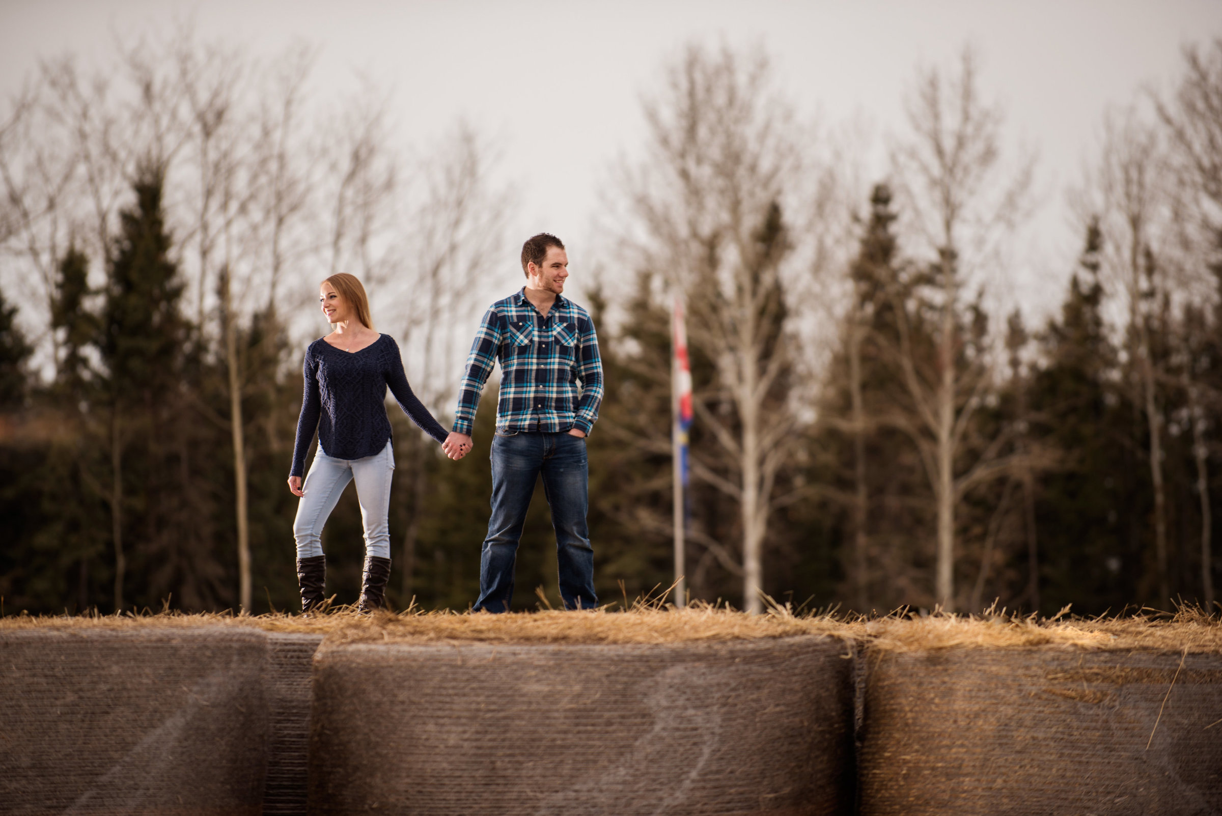 Couple standing on hay bales