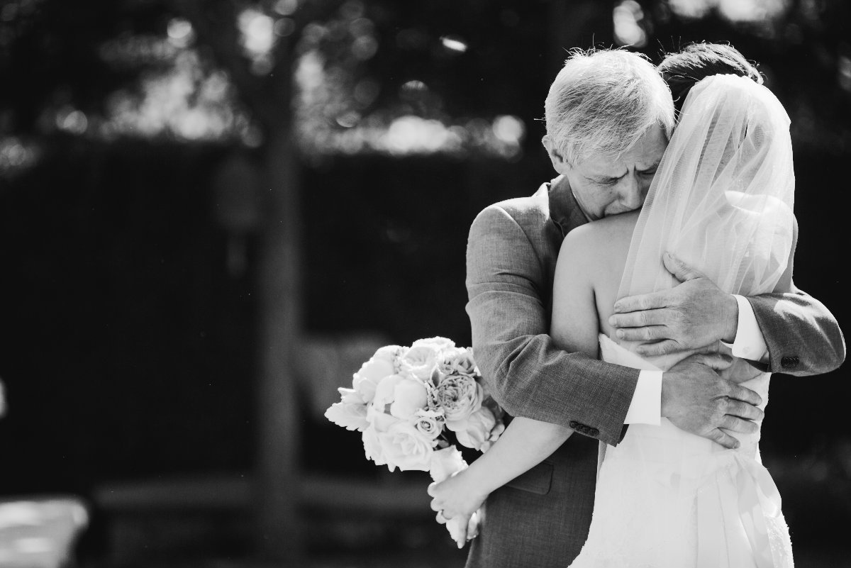 Black and white photo of father hugging his daughter as he gives her away  in California  wedding