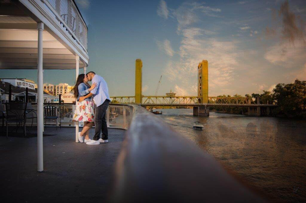 Engaged couple posing next to a pole while overlooking the Sacramento river and looking at Tower Bridge, by Sacramento wedding photographer, Philippe Studio Pro