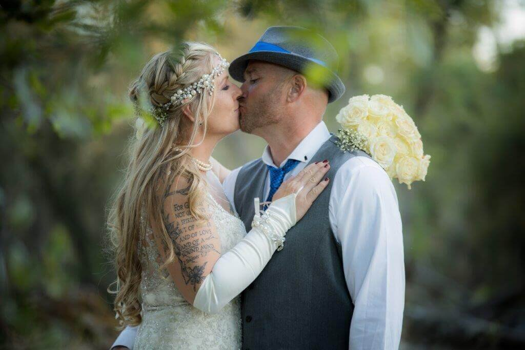 Bride and groom embrace on their wedding day for a kiss. The bride is wearing a wedding dress and the groom is wearing a white shirt, grey vest and blue top hat. They are surrounded by trees.  Sacramento wedding photographer, Philippe Studio Pro, took the photo.