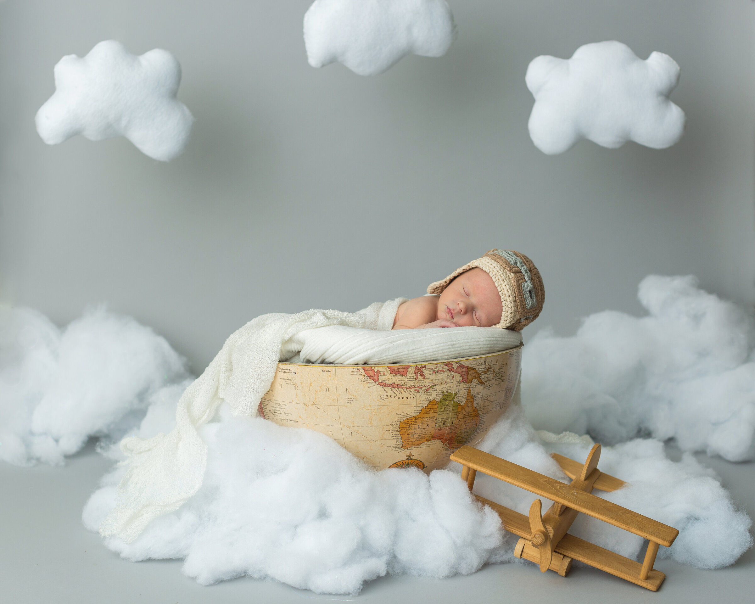 newborn posed in globe with toy airplane