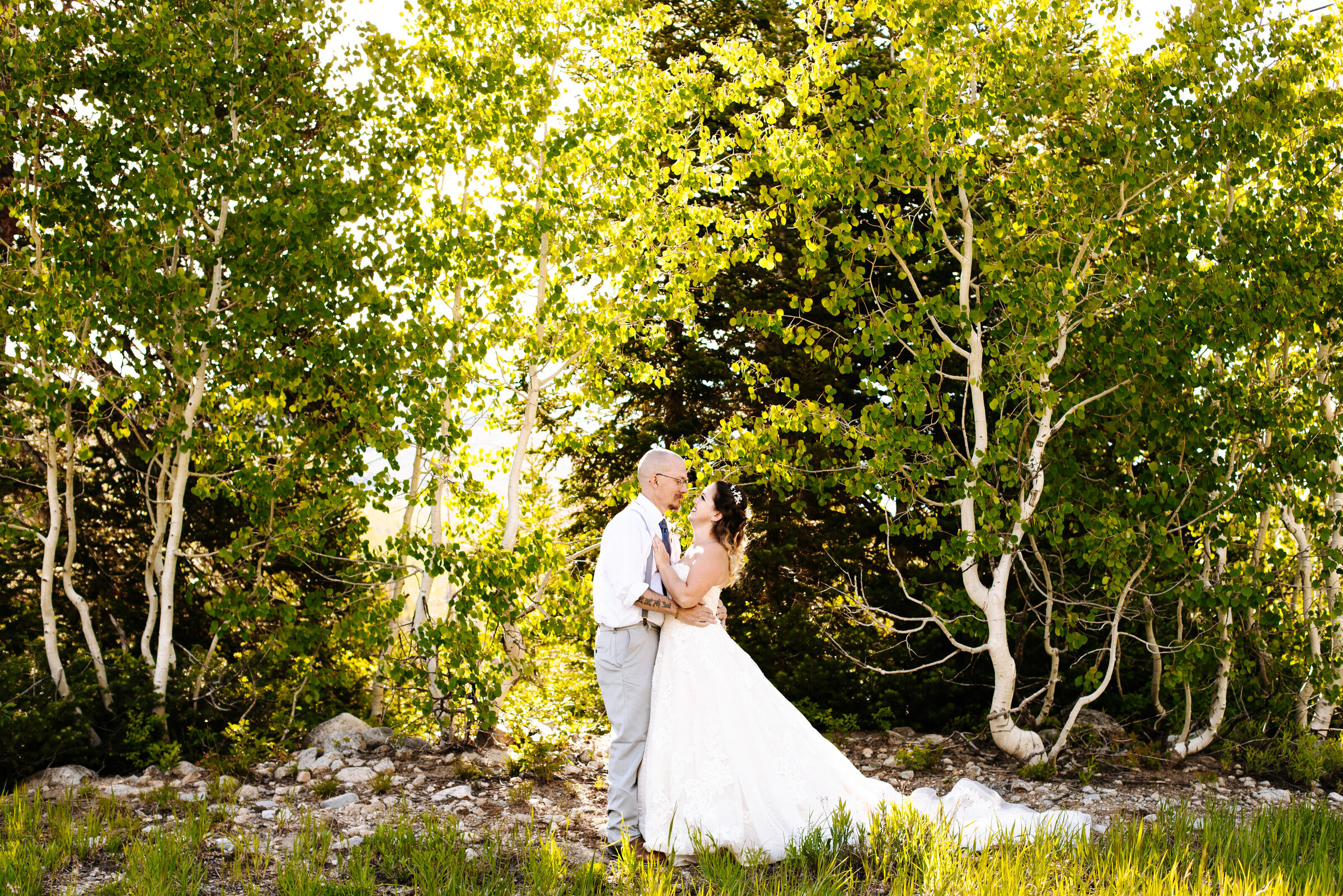 Bride and groom looking at each other and holding each other. Aspen trees surround them, they're at Solitude Mountain Resort near Park City, Utah.