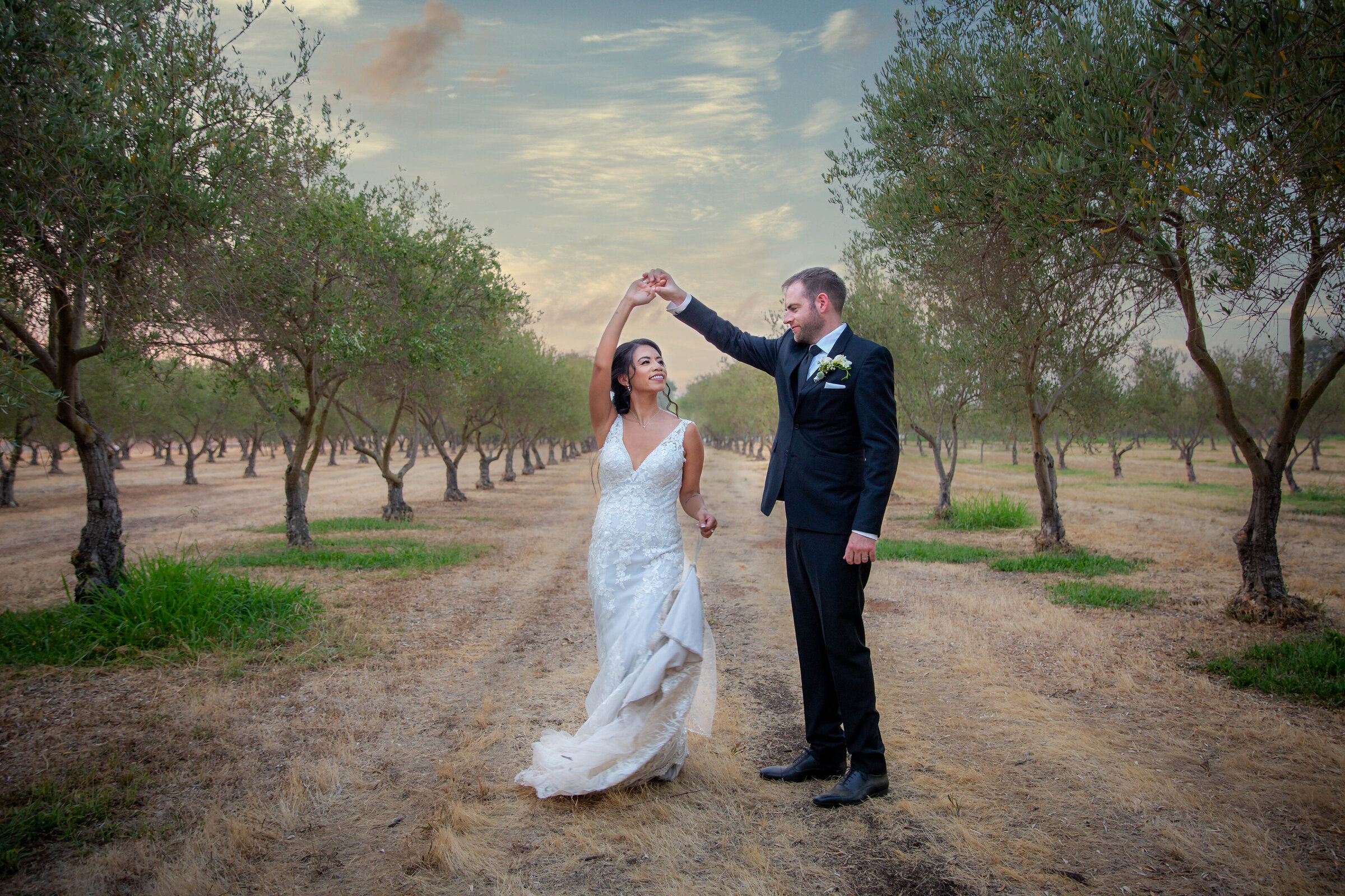 Groom twirling bride in the middle of a vineyard with the bride smiling looking at the groom at Wolfe Heights Event Center, photo by wedding photographer in sacramento ca philippe studio pro