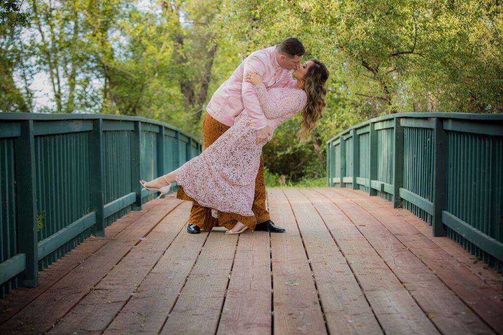 Sacramento wedding photographer, Philippe Studio Pro captures couple on wedding day in traditional filipino clothing with the groom dipping the bride on a bridge in a park surrounded by trees.