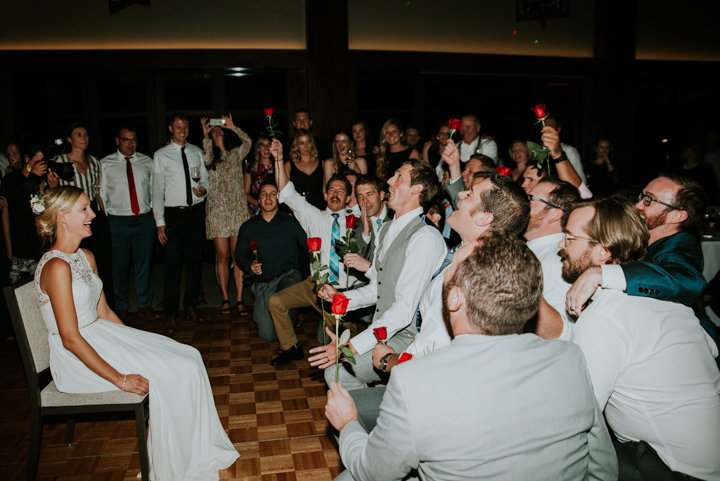 groomsmen singing to bride with roses
