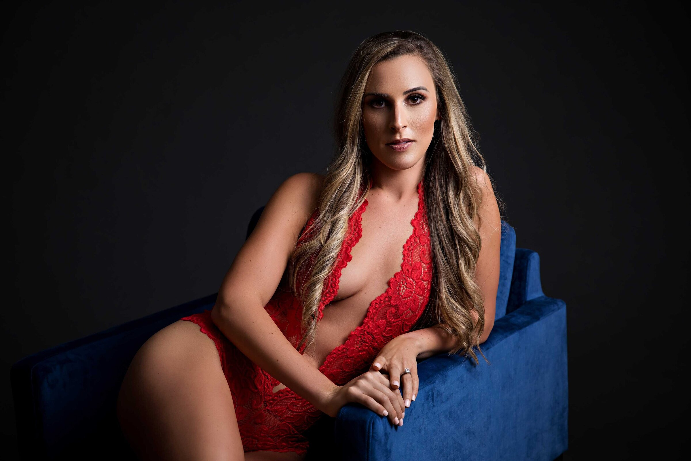 boudoir session of woman in red lace bodysuit sitting in blue velvet chair